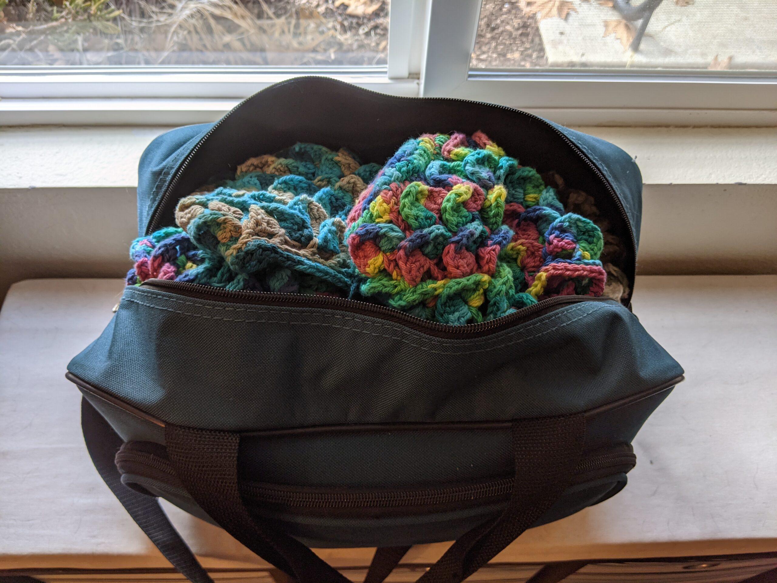 a tote bag full of crochet dice bags